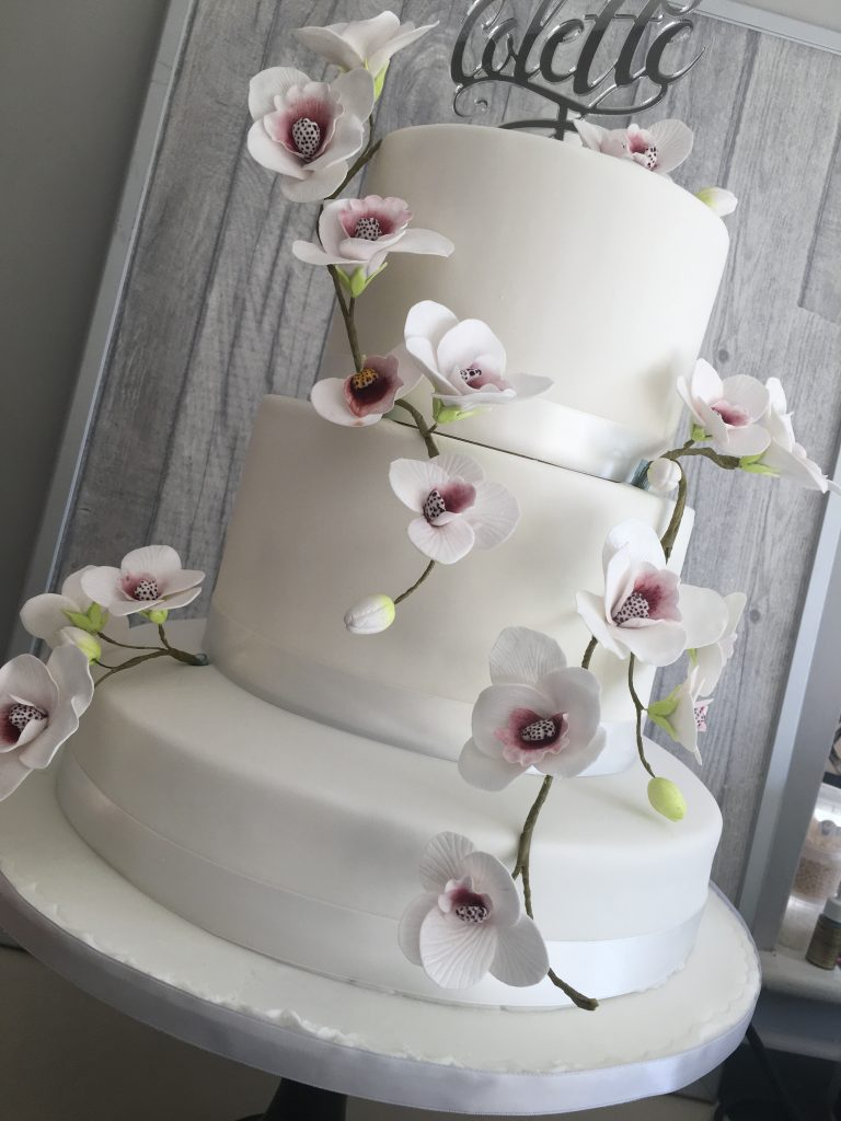 Ice White wedding cake with moth Orchids